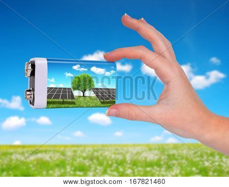 Hand holding battery with solar panels. The concept of sustainable resources.