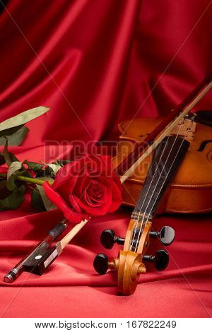 Violin (fiddle) and red rose lying on the perfect red satin fabric. String instrument.
