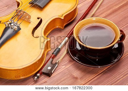 Violin and cup of coffee on a wooden background.