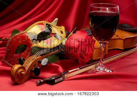 Violin (fiddle), theater mask, glass of red wine and red rose lying on the perfect red satin fabric. String instrument.