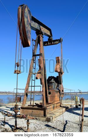 Rusty Oilfield Pumpjack (rocking horse) over a wellhead. Clear blue sky and lake background