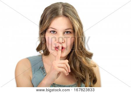 Young pretty woman is holding her finger at her lips for signing