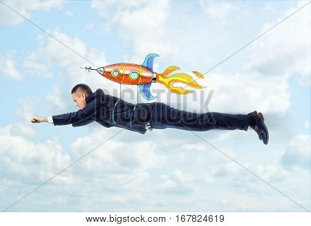 Businessman is flying on the rocket on the background of blue sky and clouds. Succes in business. Start up. Fast development