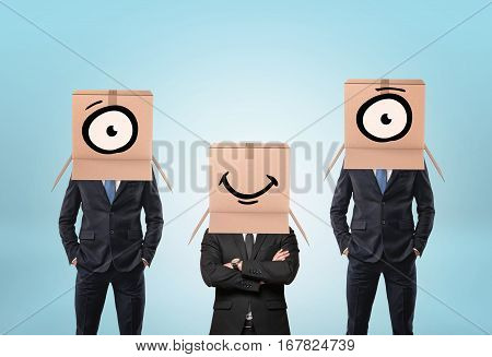 Three businessmen wearing cartons on their heads, one has a mouth drawn on it, and two others have eyes. Business and success. Corporate culture. Workplace communication.