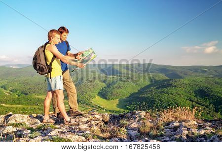 Two tourists on mountain read the map. Mens on top of cliff. Tourism concept