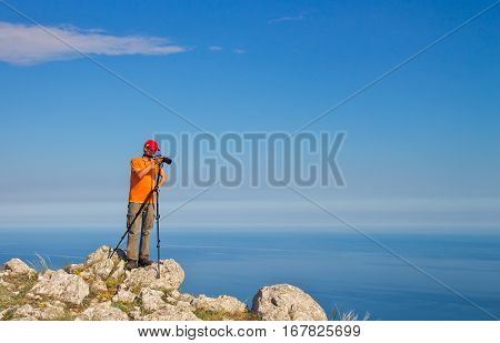 Photographer takes pictures of landscapes on mountain near the sea. The men with the camera in hot day. Man working in nature.