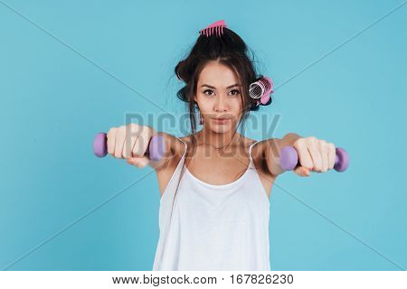 Full length portrait of a concentrated young woman with curlers holding weights and looking at camera isolated on a blue background