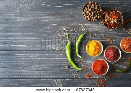 Aromatic spices in glass bowls on blue wooden background