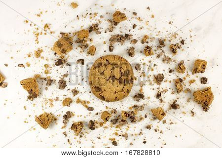 A photo of a crunchy chocolate chips cookie with crumbs around it, shot from above on a white marble background, with copyspace
