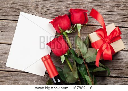 Valentines day greeting card. Red rose flowers, wine and gift box on wooden table. Top view with blank card for your greetings