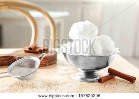 Vintage bowl with snow ice cream on table strewn with cinnamon powder