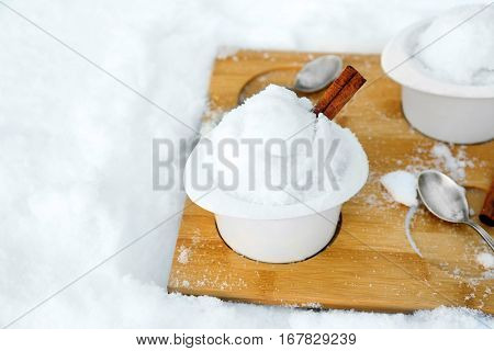Ice cream cups with snow on wooden board outdoors