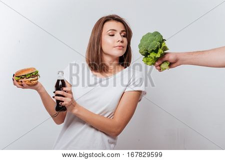 Image of hungry young lady standing over white background while holding fastfood and look at broccoli