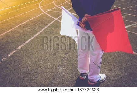 Running Assistant Referee Or Linesman Running With Flag White And Red On Running Track And Field.