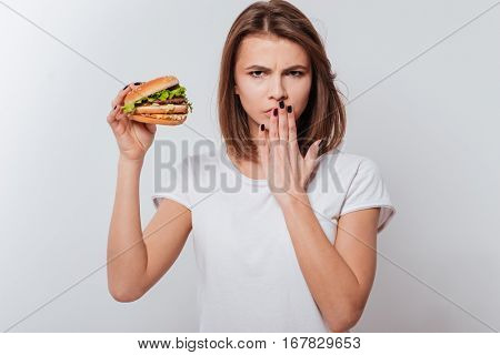 Image of angry woman standing over white background while holding fastfood and covering mouth with hand