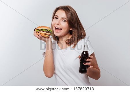 Picture of hungry young woman standing over white background while eating fastfood