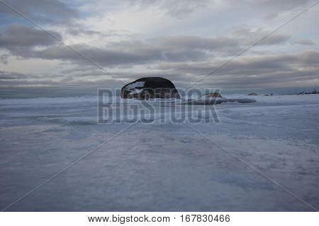 A rock sits in frozen shallow Lake Michigan waters