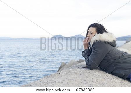 Woman On A Seawall Looking Away To The Sea.