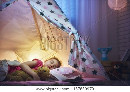 Adorable little child girl is napping in the tent. Quiet sleep with teddy bear after reading book.