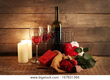 St. Valentines Day concept. Composition of wine, roses, candles and gift box on wooden table
