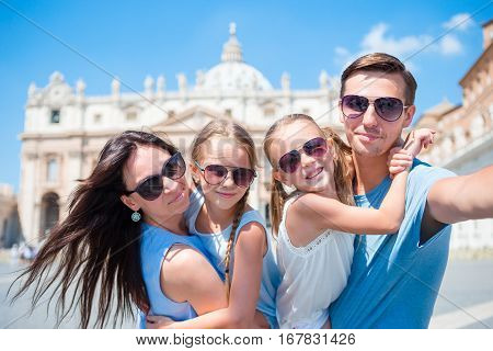 Happy family taking selfie in Vatican city and St. Peter's Basilica church, Rome, Italy