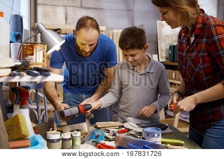 Parents and son tinkering together in workshop at home.