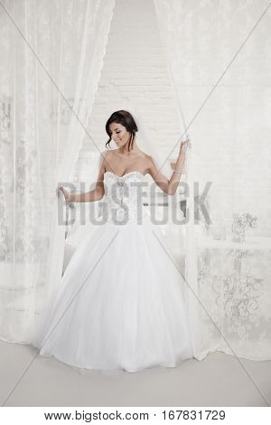 Beautiful bride in wedding gown standing among white sheer curtains. Full size.