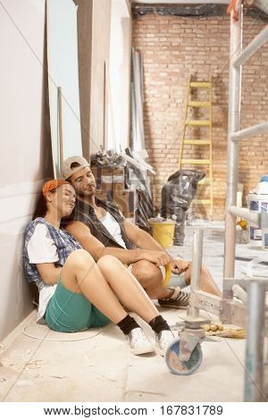 Exhausted young couple resting on floor at home under renovation.