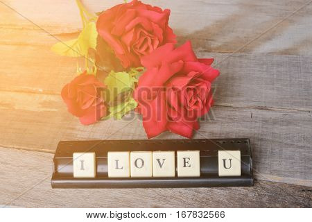 I love u wording by crossword on old wooden board with artifical roses background. Sunshine effect. Love and romance Valentine's day concept.