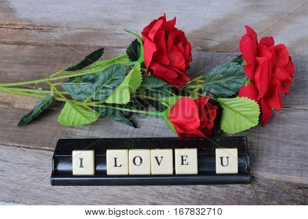 I love u wording by crossword on old wooden board with artificial red roses background. Love and romance Valentine's day concept
