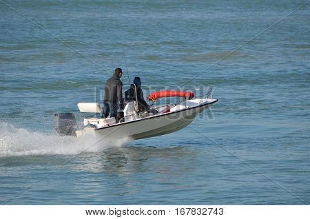Young couple enjoying a high speed dash across the florida intra-coastal waterway near Miami Beach in a small outboard powered fishing skiff.
