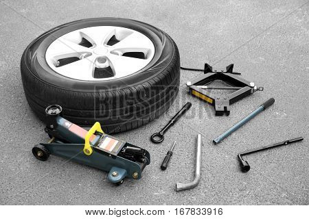 Car wheel with tools on asphalt background