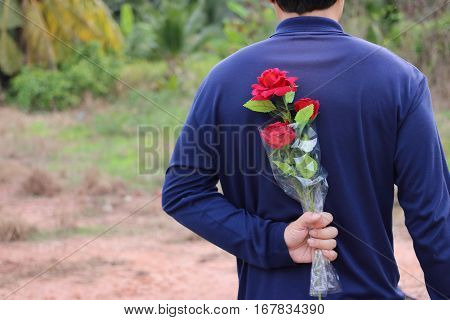 Back view of young handsome man is waiting and hold a beautiful bouquet of artificial red roses behind his back. Love and romance concept.