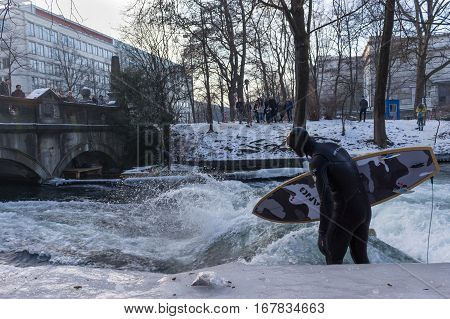 MUNICH - JANUARY 28: A surfer riding top of a wave on river Isar Munich Germany. People surfing on -10 degrees while everything around them is frozen.