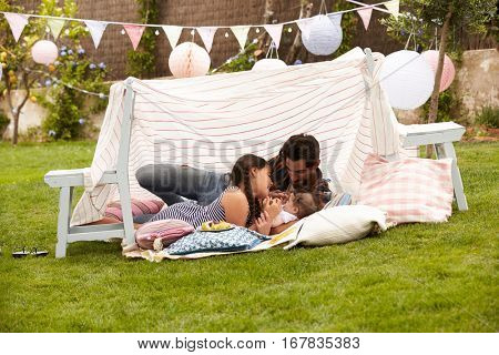 Father Playing With Daughters In Home Made Garden Den