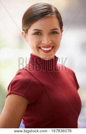 Smiling young white businesswoman in maroon dress, vertical