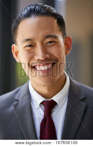 Young Asian businessman smiles to camera, close up, vertical