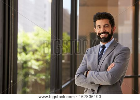 Smiling Hispanic businessman with arms crossed, to camera