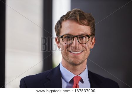 Young white businessman wearing glasses smiling, close up