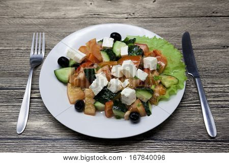 Greek salad on a white plate with fork and knife on a wooden table. Can be used as a photo for restaurant menus, bistro. European, Mediterranean cuisine