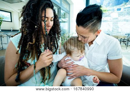Lesbian couple sitting with their baby in living room