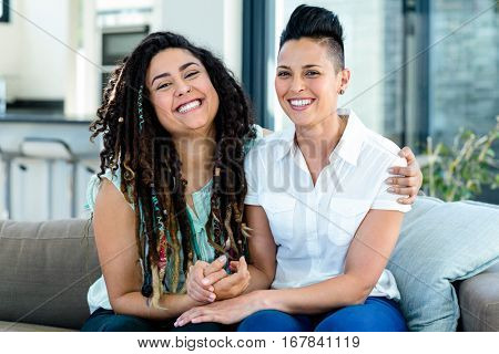 Portrait of smiling lesbian couple sitting together on sofa in living room