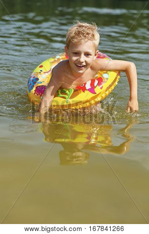 Boy learning how to swim with a floating ring in a lake in summer