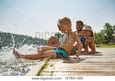 Happy family at a lake having fun and splashing water in summer