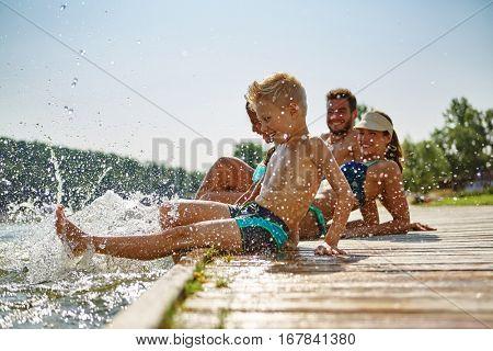 Happy family at a lake having fun and splashing water in summer
