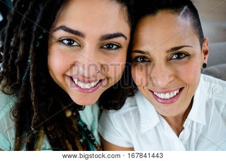 Portrait of happy lesbian couple in living room