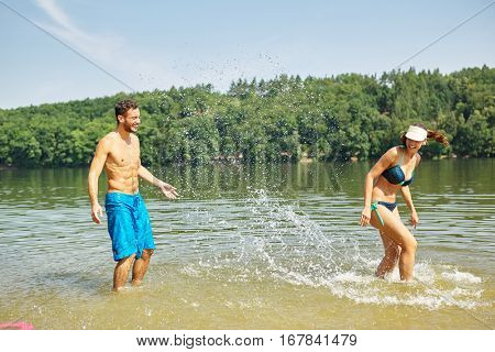 Couple splashes each other with water and have fun in summer