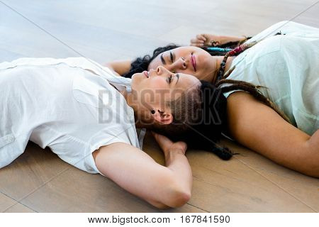 Lesbian couple in love lying on wooden floor