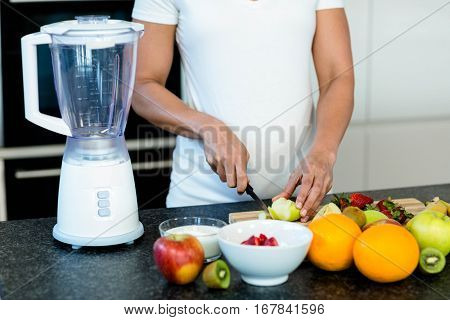 Mid section of pregnant woman cutting fruits on chopping board
