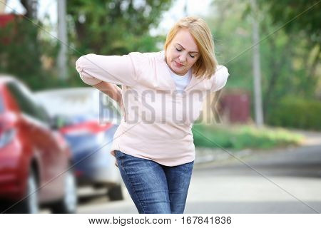 Senior woman suffering from backache outdoors